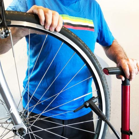 Man with bicycle wheel and pump